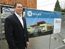 OUTLOOK PHOTO - MBank CEO and President Jef Baker shows off an artist rendering of the remodeled bank at 1290 N.E. Burnside Road in 2015.
