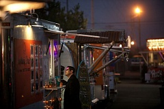 FILE - A patron waits for his order to be prepared at the Cartlandia food cart pod on Southeast 82nd Avenue in Portland after dusk. The Tualatin City Council has directed city staff to prepare a draft ordinance that would allow food carts and trucks in Tualatin but prohibit them from staying in place overnight.