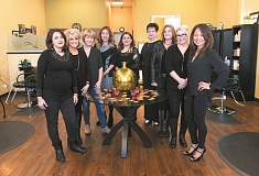 JAIME VALDEZ - Malihe Khany, middle, owner of Ziba Salon, stands with her staff at the hair salon at Progress Ridge TownSquare.