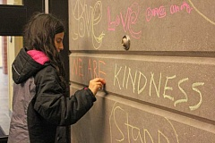 REVIEW PHOTO: JILLIAN DALEY - Faith Galderisi's daughter Gabriella, a sixth-grader at Lake Oswego Junior High, writes a positive message in chalk in the exterior entryway of Lake Oswego High School on Nov. 16. Galderisi, event organizer and a member of the Oregon Physicians Moms Group, says the action was about teaching and involving children in the fight against discrimination.