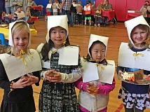 SUBMITTED PHOTO: CAROL WHITTEN - Kindergartners/pilgrims Jocelyn Howard, Ellen Seo, Katherine Jung and Alina Burke Zukle enjoy a Thanksgiving feast at Lake Grove Elementary School on Nov. 18. The event features five kindergarten classrooms and 119 students, says Carol Whitten, the Lake Grove principal. The event includes students from a combination of schools, since Lake Grove is housing all of the kinder students from Oak Creek this school year.