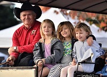 REVIEW PHOTOS: VERN UYETAKE - Larry Chafin of Sweet Home takes a group of passengers on a horse-drawn wagon ride through Lake Oswego during Saturday's Reunion Market. Joining Chafin up front are (from left) Annabelle Hudson, Charlie Hudson and Milly Thornton-Jeynes.