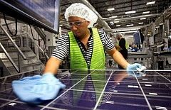 PAMPLIN MEDIA FILE PHOTO - Guiloermo Mandujano cleans and checks a solar panel at the SolarWorld production facility in Hillsboro.