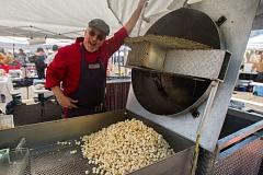 OUTLOOK PHOTO: JOSH KULLA - Mike Marselle of Munchies Kettle Corn shows off a fresh batch of popped corn Saturday at the opening weekend of the Gresham Farmers Market on the Mount Hood Community College Campus.