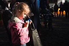 OUTLOOK PHOTO: JOSH KULLA - A girl is highlighted by the sun Saturday morning as she checks out the candy insider her Easter egg at the Professional Firefighters' annual egg hunt at West Gresham Elementary School.