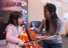 FILE PHOTO - Finleigh Hanawa tries her hand at the cello at the Fairview Library.