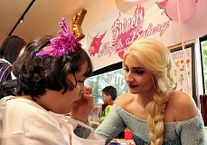 REVIEW PHOTO: VERN UYETAKE - Aaliyah Salgado (left) gets her face painted by a snow queen from Dragon Theater Princesses on Monday at the grand opening celebration for her Sweet Angels Bakery in Lake Oswego.