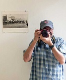 ESTACADA NEWS PHOTO: EMILY LINDSTRAND - Larry Cutler has been interested in photography for the majority of his life. Here, he poses with his camera and a photo of historic downtown Estacada.
