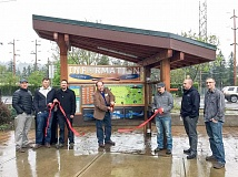 ESTACADA NEWS PHOTO: EMILY LINDSTRAND - Mayor Sean Drinkwine cuts the ribbon during the opening ceremony for the new interactive map at the Estacada  Cycling Station Plaza on Monday, April 24.
