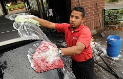 REVIEW FILE PHOTO: VERN UYETAKE - Employees washed cars by hand at the Lake Oswego Car Wash on Boones Ferry Road, which closed for good on March 31 after 25 years in business.