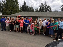 SUBMITTED PHOTO - Nigel Guisinger, owner of Willamette Valley Appliance (blue shirt in center), cuts the ribbon on his newly acquired business (formerly known as Walts Applicance), on May 4, joined by Mayor Krisanna Clark on his left and Lana Painter, executive director of the Sherwood Chamber of Commerce to the left of Clark.