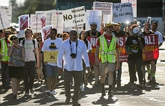 OUTLOOK PHOTO: JOSH KULLA - March organizer Juan Rogel (middle) leads demonstrators down Southeast Stark Street Tuesday afternoon as they protest recent raids by federal Immigration and Customs Enforcement agents in the Rockwood area.