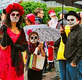 DAVID F. ASHTON - Ghouls-in-waiting: The Toporowskis - Julie, Jillian, and John - pause for a photo during this years rain-soaked Moreland Monster March. In the background, a wayward Santa seems unfazed by this Nightmare Before Christmas.