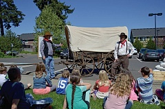 SPOTLIGHT PHOTO: NICOLE THILL - Tim McCann and Don Scott, volunteers with the Curtis Heritage Education Center, talk to students in Erika Reardon's fourth-grade class about the history of the Oregon Trail, Thursday, April 21. The volunteers brought a 170-year-old covered wagon to the school to teach students more about pioneers on the Oregon Trail.