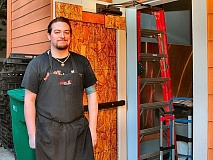 DAVID F. ASHTON - Sellwood Killer Burger crew member Dan Rickey shows the now boarded-up back door that burglars kicked in to steal their safe - and the days proceeds.