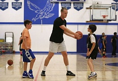 TRIBUNE PHOTO: JONATHAN HOUSE - Alex Foster, a 6-8 pro basketball player, instructs youth attending a camp he runs at his alma mater, Catlin Gabel.