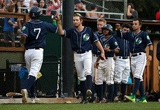 Portland Pickles catcher Andrew Garcia (left) is greeted by teammates after scoring during Thursday night's game at Walker Stadium.