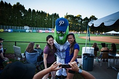TRIBUNE PHOTO: ADAM WICKHAM - Fans get their photo opportunity with Dillon, mascot of the Portland Pickles, during the season finale Thursday night at Walker Stadium.