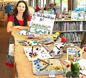 DAVID F. ASHTON - Rachel Ginocchio stands with some of the curated entries from the Sellwood Bridge Art Project, as displayed in August at the Sellwood Branch Library.