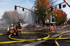 TRIBUNE PHOTO: JAIME VALDEZ - Portland firefighters hosed down what was left of a building at the corner of Northwest 23rd Avenue and Glisan Street Wednesday morning, nearly two hours after a natural gas explosion rocked the area.