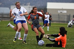 PAMPLIN MEDIA: LON AUSTIN - Gladstone's Chloe Villanueva (2) crashes the goal as Crook County keeper Josie Graydon makes a sliding save with defensive support from Tiffany Smith (19) in Thursday's Tri-Valley Conference match in Prineville.