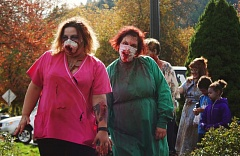 OUTLOOK PHOTO - Sunshine O'Connor, left, and Julie Price lead the 2016 Gresham Zombie Walk, which they organized, dressed as undead nurses.