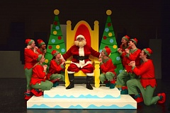 PHOTO BY KARMIN TOMLINSON - Santa, played by Sam Levi, is surrounded by adoring elves, who also sing and move scenery around in OCHS's 'Miracle on 34th Street,' opening on Dec. 7.