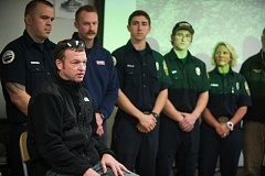 OUTLOOK PHOTO: JOSH JULLA - Surrounded by some of the first responders who rescued him, Bill Crane details the injuries that required he wear a back brace for three months.