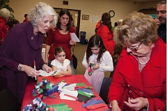 PHOTO BY DOUG OLMSTEAD - At last year's Winter celebrations, Judith Kallio, left, instructs attendees how to make colorful paper chains for holiday tree decorating.