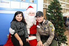 PHOTO COURTESY: CCSO - Clackamas County Sgt. Erin Brisben (right) joins a child in asking Santa for presents in a 'Shop with a Cop' tradition.