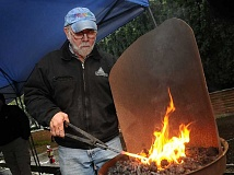 STAFF PHOTO: VERN UYETAKE - Fred Martin places a piece of gun metal into the hot coals.