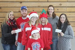 WILL DENNER/MADRAS PIONEER - From left, Angela Harris, Tim Nelson, Elli Williams, Ava Williams, Lexi Williams, Heather Williams and Karen Affeldt pose with two checks worth $6,500 that will be donated to the Madras Swim and Water Polo teams.