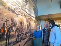 PHOTO BY ELLEN SPITALERI - Bethany Nemec points out details in the mural in the entry hall at the End of the Oregon Trail Interpretive & Visitor Information Center to Jerry Herrmann, center, and Adam Doty.