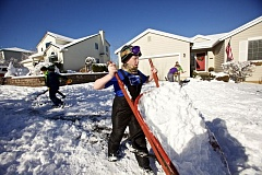 TIMES PHOTO: JAIME VALDEZ - Aidan Kelly, 11, dumps snow from a wheelbarrow as he and his brother, Finn (not pictured) and their neighborhood friends help shovel their Grandpa John Hunter's driveway.