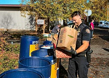 DAVID F. ASHTON - PPB East Precinct Neighborhood Response Team (NRT) Officer Ryan Mele drops donated goods into a Sunshine Division barrel.