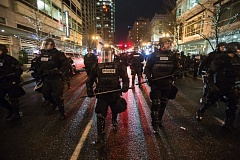 TRIBUNE PHOTO: JOSH KULLA - Police decked out in riot gear march down Broadway Street in downtown Portland Friday night following protests against the inaugaration of Donald Trump as President. An estimated 10,000 or more people took part in the protest.