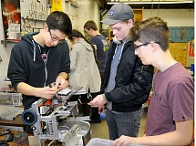 SETH GORDON - Joe Murphy, Alexander Berger and Kyle Hatch tinker with their robot at Newberg High School last week. The trio are part of the Iron Men Mark2 team, which itself is one of four NHS robotics teams that will compete at super qualifying tournaments this weekend in hopes of advancing to the First Tech Challenge state meet.
