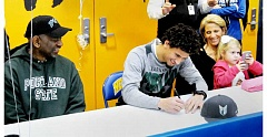 PAMPLIN MEDIA GROUP: SETH GORDON - Newberg High senior Anthony Adams fills out the paperwork to play football at Portland State during a signing ceremony.