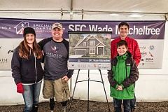 COURTESY OF THE GARY SINISE FOUNDATION - Retired U.S. Army Sgt. Wade Mitcheltree, second from left, poses with wife Katie and sons Joseph, 14, and Ethan, 11, with a rendering of the house being built for them in Tigard at a groundbreaking ceremony Jan. 11.