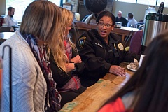 FILE - Tigard Police Officer Kristan Renell speaks with community members during a 'Coffee with a Cop' outreach event last year at Well & Good Coffee House.