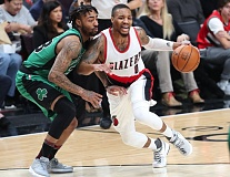 TRIBUNE PHOTO: JAIME VALDEZ - Trail Blazers guard Damian Lillard (right) drives on the Boston Celtics' James Young.