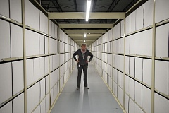 OUTLOOK PHOTO: JOSH KULLA - Plant manager Carol Suckow stands in a long row of shelves in a second-floor storage area for smaller Subaru parts. The boxes are not yet in use, but will be once the warehouse fills up with 50,000 different parts.