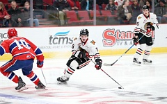 COURTESY: BRYAN HEIM/PORTLAND WINTERHAWKS - Portland Winterhawks forward Ryan Hughes moves the puck away from Spokane Chiefs forward Ethan McIndoe during a Friday game at Moda Center.