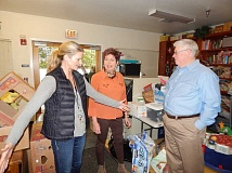 BABARA SHERMAN - Standing in the Good Neighbor Center's multi-purpose room where classes are held, homework is completed and donations are sorted and stored, Heidi Guffey (left), the Good Neighbor Center's volunteer coordinator, talks to Sandy Brewer, who is in charge of this year's Summerfield Women's Golf Club's charity fundraiser, and Jack Schwab, the center's executive director.