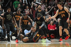 TRIBUNE PHOTO: JOSH KULLA - Atlanta Hawks teammates come celebrate with Paul Millsap (on floor), after his last-second basket forced overtime Monday night at Moda Center.