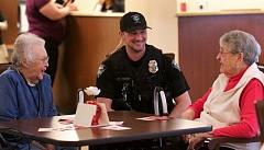 TIMES PHOTO: JAIME VALDEZ - Tualatin Police Officer Shawn Fischer visits with Marquis Tualatin Assisted Living residents Betty Charters, left, and Dorothy Shelton during a Valentine's Day ball at the retirement facility.