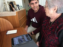 TRIBUNE PHOTO: SHASTA KEARNS MOORE - Lincoln High School junior Amahn Enayati teaches 87-year-old Lily Irinaga how to use basic functions on her iPad. Enayati wants more teens to join Teen Tech Help to connect with seniors.