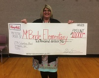 COURTESY PHOTO - Principal Lisa Tyler holds up a homemade giant check after a school assembly at McBride Elementary School. The school recently won $10,000 in a sweepstakes contest sponsored by Campbell's Soup Company.