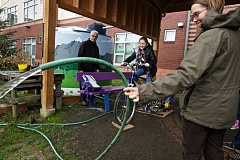 TIMES PHOTO: JAIME VALDEZ - Pam Soderquist, a teacher at Tualatin Elementary School, holds a garden hose as water flows out of it, pumped from the energy produced from fifth-grader Ruby Heathcott pedaling on a stationery bike at the Tualatin Community Garden.