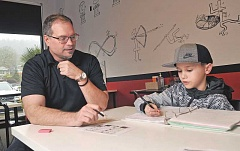 PHOTOGRAPHS BY VERN UYETAKE - Mathnasium Owner/Director Bruce Withycombe works with fourth-grader Tripp Moussavi.